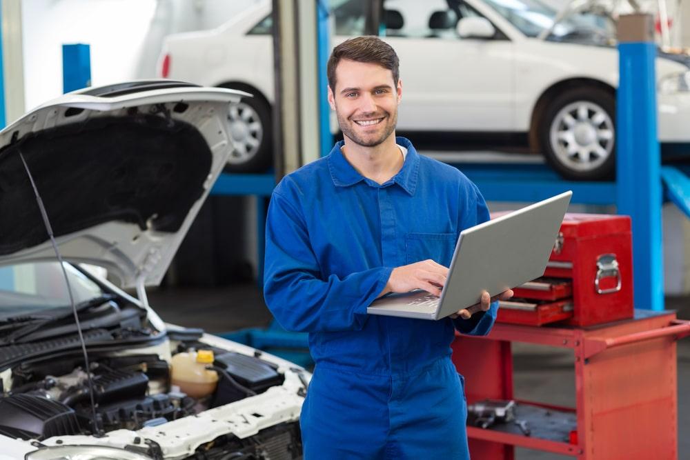 Mechanic using his laptop at the repair garage